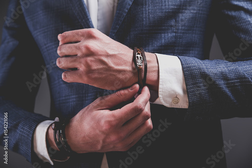 Fotografía  Fashion portrait of young businessman handsome model man dressed in elegant blue suit with accessories on hands posing on gray background in studio