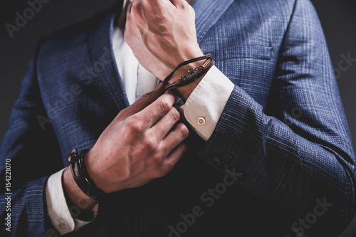 Fotomural  Fashion portrait of young businessman handsome model man dressed in elegant blue suit with accessories on hands posing on gray background in studio