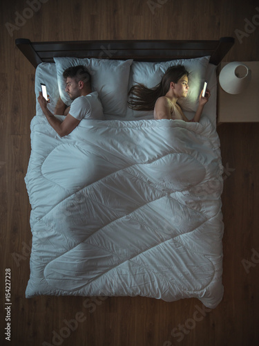 The Upset Couple With Phone Lie On The Bed View From Above Buy