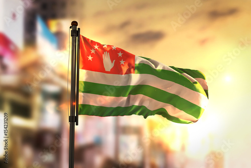 Abkhazia Flag Against City Blurred Background At Sunrise Backlight Wallpaper Mural