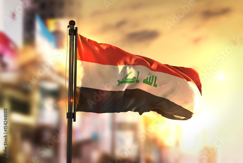Fotografie, Tablou Iraq Flag Against City Blurred Background At Sunrise Backlight