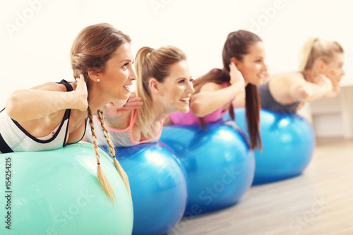 Group of smiling people doing aerobics with balls