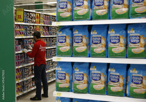 Employee sorts products at grocery store which is 100th