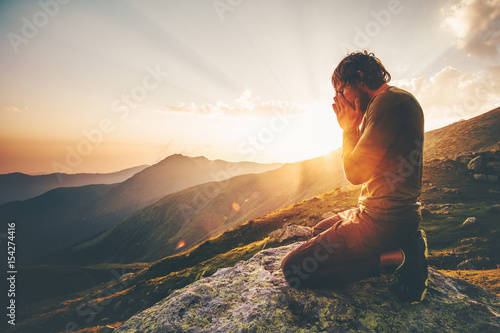 Vászonkép Man praying at sunset mountains Travel Lifestyle spiritual relaxation emotional
