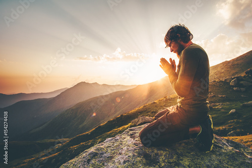 Obraz na plátně Man praying at sunset