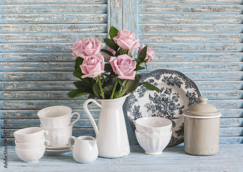 Foto-Plissee - Pink roses in a white enameled pitcher, vintage crockery on blue wooden rustic background. Kitchen still life in vintage style. Flat lay (von okkijan2010)