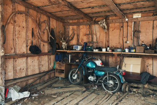 Tuinposter Fiets Old Blue-Green Motorbike In Picturesque Barn.Vintage Motorcycle In Old Hangar Against A Wall With Deer Antlers, A Bison Head And Many Interesting Rare Objects. Old Barn With Old Moped And Wooden Walls