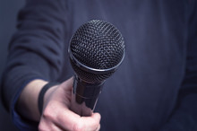 Journalist Making Speech With Microphone And Hand Gesturing Concept For Interview.