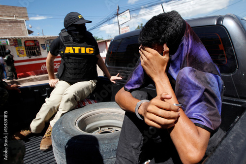 Investigative Police Agent Escorts A Suspected Ms 13 Gang Member Detained During Operation Hunter Before Taking Him To Police Facilities For An