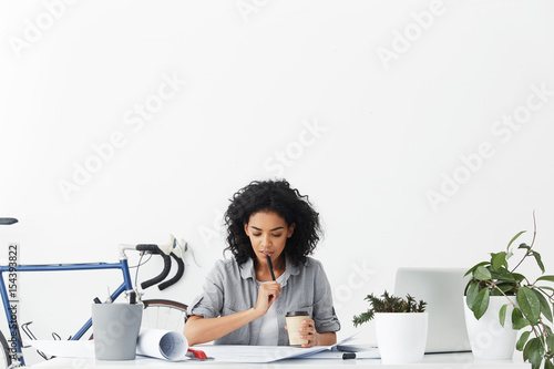 Fotografía  Fashionable female Afro American student doing her homework designing new buildings sitting in cosy home interior drinking coffee holding pen and having thoughtful expression