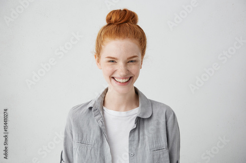 Beautiful ginger freckled girl with mysterious smile posing indoors at blank grey studio wall. Pretty woman with hair bun smiling broadly, showing white straight teeth, enjoying leisure time at home
