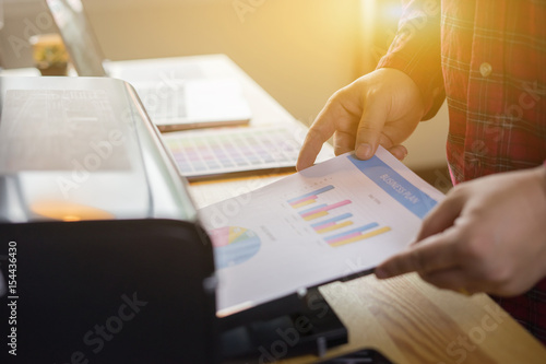 Fotografía  Businessman analyzing investment charts and business plan with printer