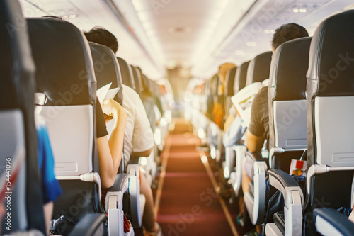 In de dag Vliegtuig passenger seat, Interior of airplane with passengers sitting on seats and stewardess walking the aisle in background. Travel concept,vintage color,selective focus