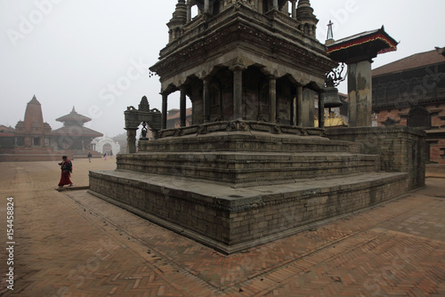 A worshiper walks past a temple after her early morning prayer in