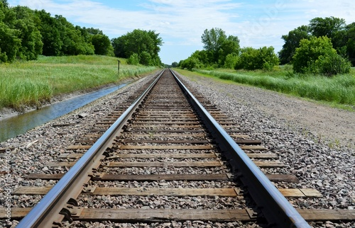 Railroad Railroad tracks on a green and rural summer countryside
