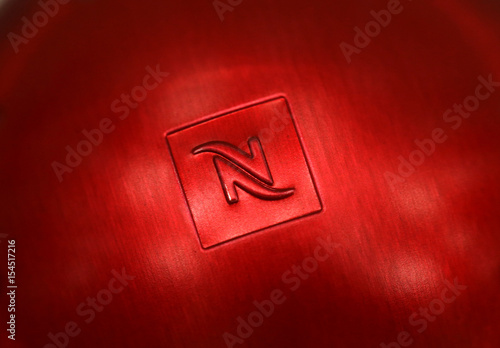a logo is pictured on a nespresso coffee pod buy this stock photo