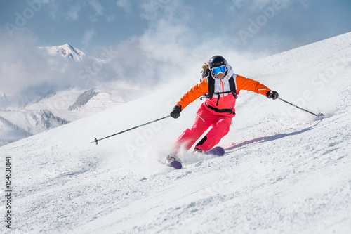 Foto op Canvas Wintersporten Female skier on a slope in the mountains