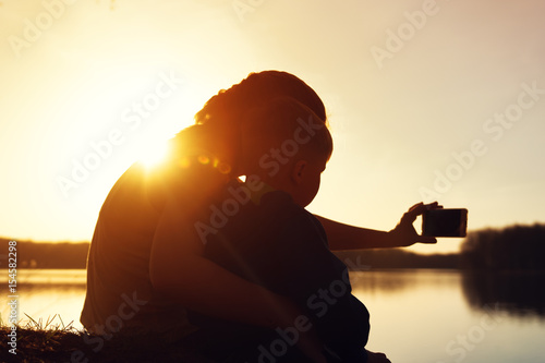 Fototapety, obrazy: Mother and son watching sunset and making selfie