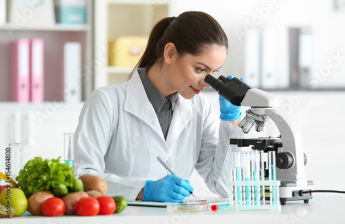 Fotografía  Young female nutritionist testing food samples in laboratory