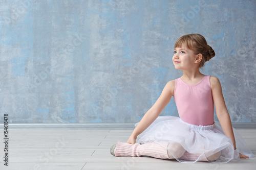 Cute little ballerina sitting on floor in dance studio Fototapet