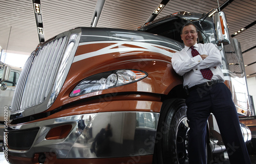 Navistar CEO Lewis Campbell poses by a truck in the lobby at the