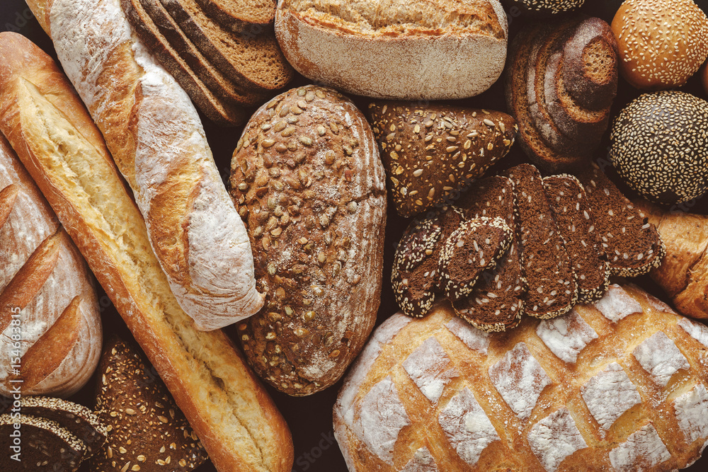 Bread background, top view of white, black and rye loaves