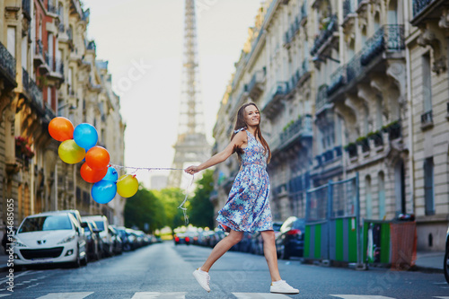 Beautiful young girl with colorful balloons running across the street in Paris Canvas Print