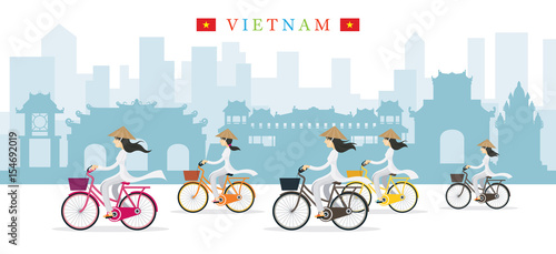 Photo  Vietnamese Women with Conical Hat Ride Bicycles, Landmarks Background