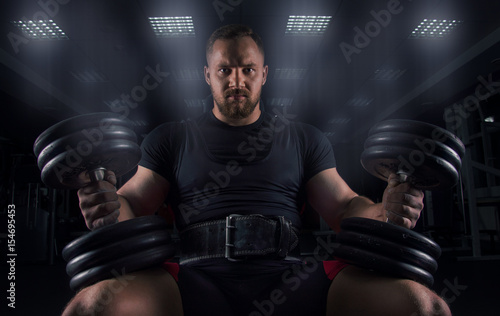 Photo Impressive athlete sits on a bench with two dumbbells on his legs