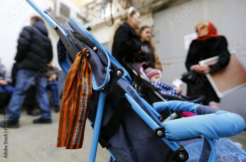 A ribbon of St  George is seen on a pram as people queue to apply