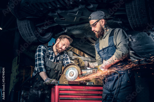 Photo  Two b mechanics working with an angle grinder in a garage.