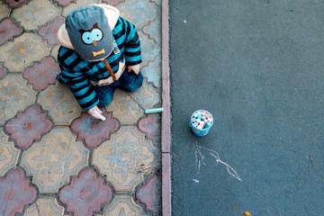 весной на детской площадке на асфальте ребенок мальчик рисует мелом разными мелками рисунки