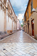 Cozy and empty narrow street between two stone houses on a summer morning. Dramatic cloudy sky. Zadar center, Croatia