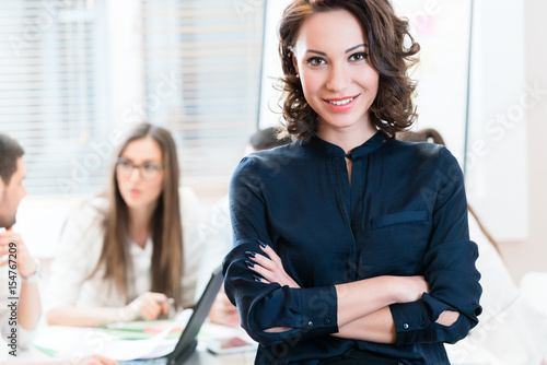 Manager with her team working in the office looking into camera