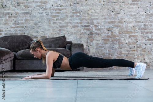 Fényképezés  Side view of slim female athlete standing in plank position on floor strengtheni