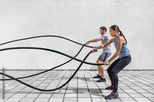 Photographie  Fitness people exercising with battle ropes at gym