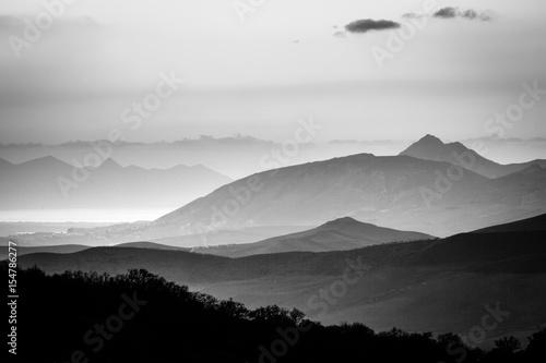 Czarno-biały panoramiczny widok mglisty krajobraz górski i sylwetki. Ficuzza, Sycylia, Włochy