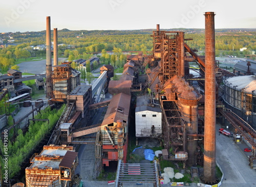 Photo sur Toile Les vieux bâtiments abandonnés Abandoned ironworks factory with forest in the background