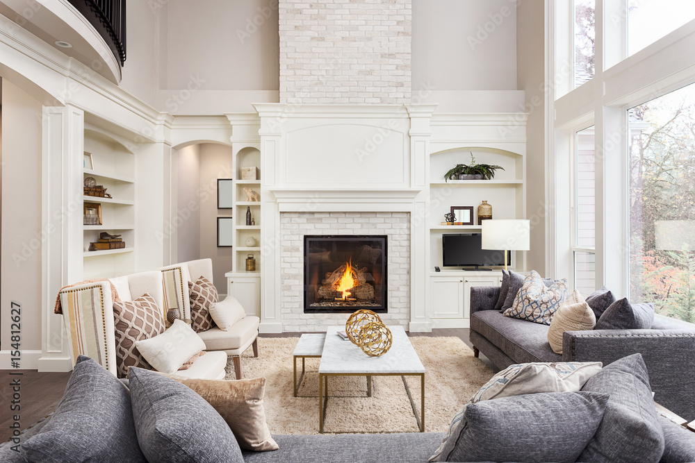 Fototapety, obrazy: Beautiful Living Room in New Luxury Home with Fireplace and Roaring Fire. Large Bank of Windows Hints at Exterior View
