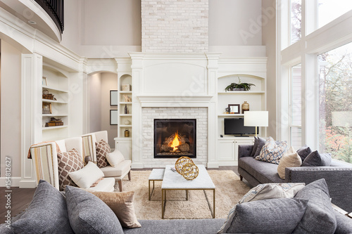 Beautiful Living Room in New Luxury Home with Fireplace and Roaring Fire. Large Bank of Windows Hints at Exterior View - Buy this stock photo and explore similar images at Adobe Stock