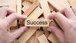 success word written and hand on woodenblock