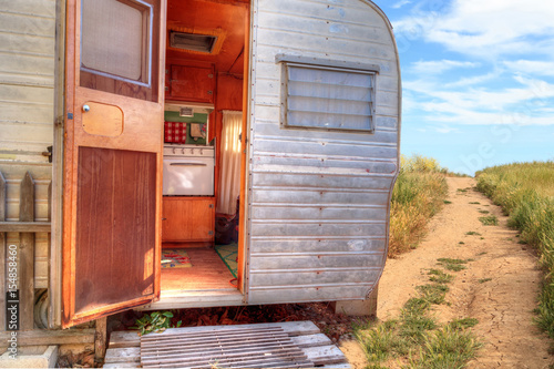 Small retro caravan camper used as a tiny house on road trips Plakat