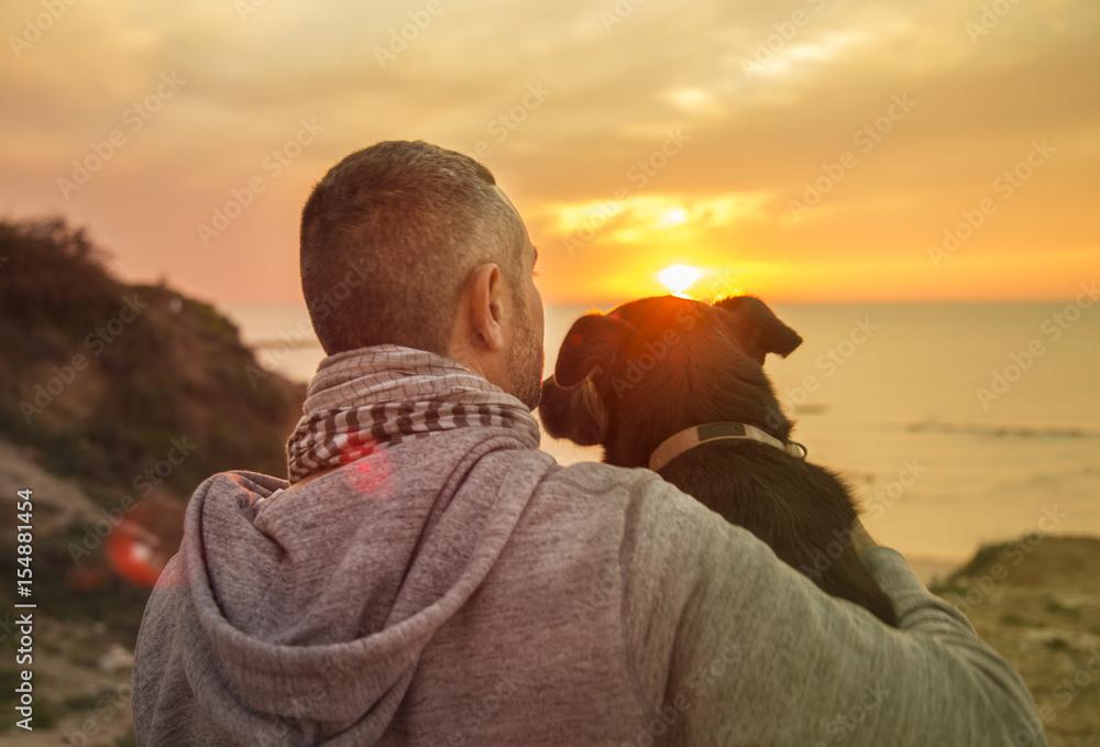 Fototapeta Man and his faithful dog enjoying an ocean sunset