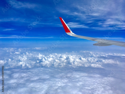 Poster Afrique du Sud airplane wing flying above the clouds with blue sky.