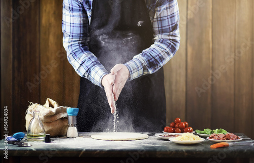 Foto op Canvas Gymnastiek man in an apron preparing a pizza, knead the dough and puts ingredients