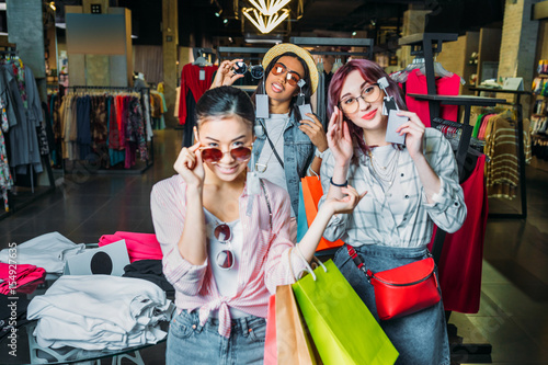 Plakat wielokulturowe dziewczyny hipster wybierając okulary w butiku, koncepcja koncepcja zakupy przyjaciół