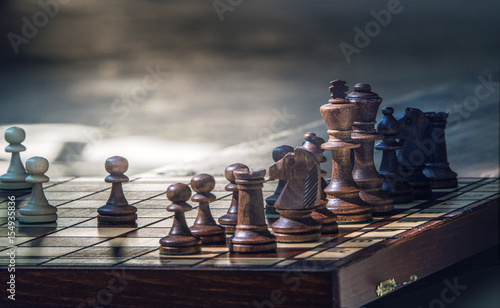 Vászonkép Wooden chess pieces on a wooden chessboard outdoor at the sunny day