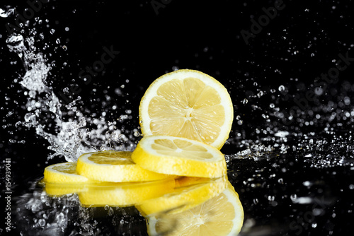 Staande foto Vlees Close-up view of fresh sliced lemon with water drops isolated on black