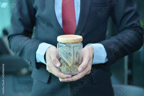 Fotografie, Obraz  Businessman holding and saving money banknotes in a wooden jar