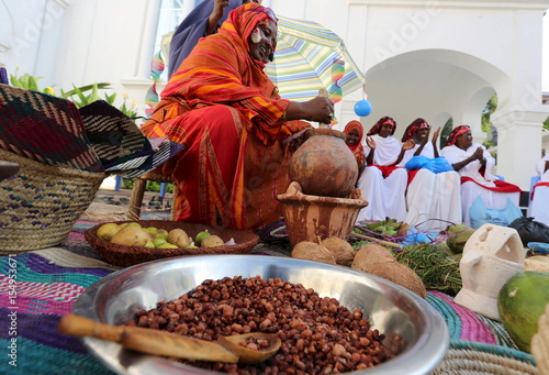 A Somali woman shows traditional items and food during an